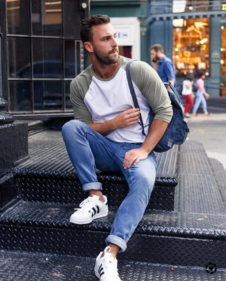 How to wear: navy canvas backpack, white leather low top sneakers, blue jeans, olive long sleeve t-shirt
