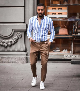 How to wear: brown sunglasses, white leather low top sneakers, brown chinos, white and blue vertical striped long sleeve shirt