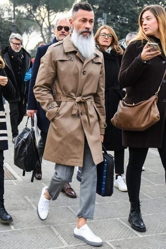 Men's Looks & Outfits: What To Wear In a Dressy Way: A tan trenchcoat and grey dress pants are a polished look that every modern gentleman should have in his closet. White leather low top sneakers will give a more laid-back vibe to an otherwise traditional look.