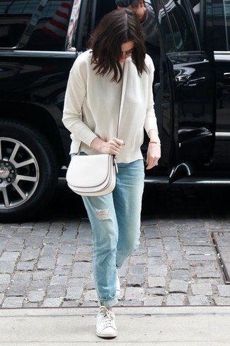 How to wear: white leather crossbody bag, white low top sneakers, light blue ripped boyfriend jeans, white crew-neck sweater