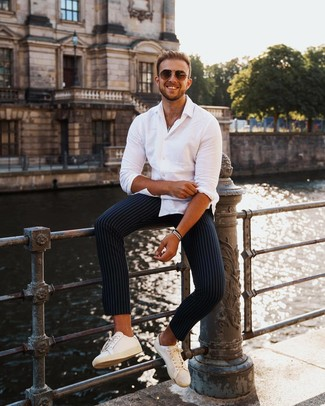 How to wear: brown sunglasses, white leather low top sneakers, navy vertical striped chinos, white long sleeve shirt