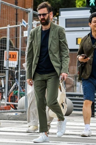 How to Wear White Canvas Low Top Sneakers For Men: For an ensemble that's super straightforward but can be styled in a ton of different ways, rock an olive suit with a navy crew-neck t-shirt. When this look is too much, tone it down by finishing with white canvas low top sneakers.