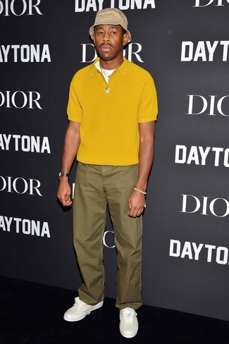 How to wear: beige bucket hat, white leather low top sneakers, olive chinos, mustard polo