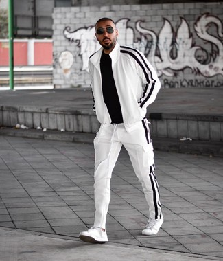 How to wear: black sunglasses, white leather low top sneakers, white and black track suit, black crew-neck t-shirt