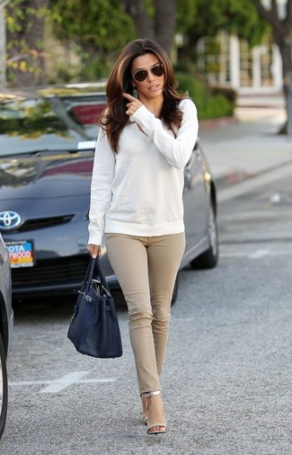 How to wear: white v-neck sweater, beige skinny jeans, silver leather heeled sandals, black leather tote bag