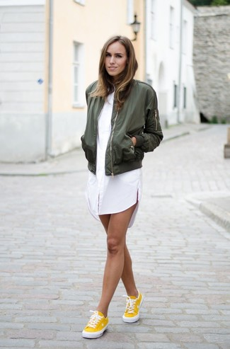 How to wear: yellow low top sneakers, white shirtdress, olive bomber jacket